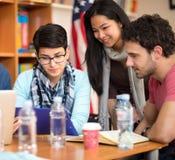 Estudiantes que intercambian opiniones sobre tarea fotografía de archivo libre de regalías