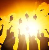 estudiantes que lanzan los casquillos de la graduación en el aire imágenes de archivo libres de regalías