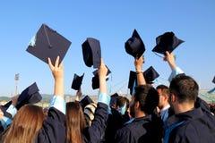 Estudiantes que lanzan los sombreros de la graduación Imagen de archivo