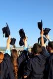 Estudiantes que lanzan los sombreros de la graduación Imágenes de archivo libres de regalías