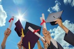 Estudiantes que lanzan los sombreros de la graduación Foto de archivo libre de regalías