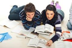 Estudiantes que leen un libro en suelo Imágenes de archivo libres de regalías