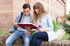 Estudiantes que leen un libro junto Fotos de archivo libres de regalías