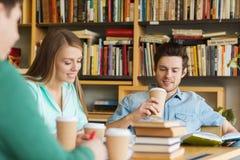 Estudiantes que leen y que beben el café en biblioteca Fotos de archivo libres de regalías