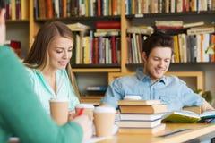 Estudiantes que leen y que beben el café en biblioteca Imagenes de archivo