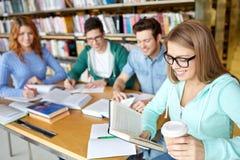 Estudiantes que leen y que beben el café en biblioteca Foto de archivo libre de regalías