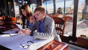 Estudiantes que llaman al profesor por smartphone y que trabajan con proyecto de la arquitectura almacen de video
