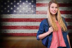 estudiantes que llevan el bolso contra fondo de la bandera americana Foto de archivo