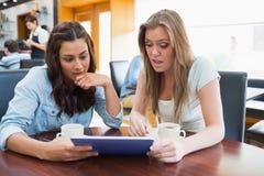 Estudiantes que miran algo el chocar en la tableta en cantina Imagen de archivo libre de regalías