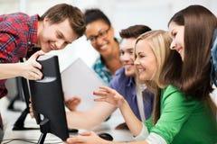 Estudiantes que miran el monitor de computadora la escuela Fotos de archivo