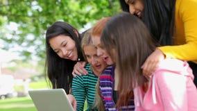 Estudiantes que miran el ordenador portátil junta exterior y la risa almacen de metraje de vídeo
