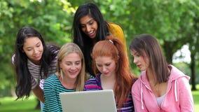 Estudiantes que miran el ordenador portátil junto afuera almacen de video