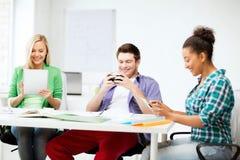 Estudiantes que miran en los dispositivos la escuela Fotos de archivo
