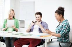 Estudiantes que miran en los dispositivos la escuela Imagen de archivo