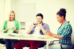 Estudiantes que miran en los dispositivos la escuela Fotos de archivo libres de regalías