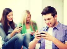 Estudiantes que miran en los dispositivos la escuela Imágenes de archivo libres de regalías