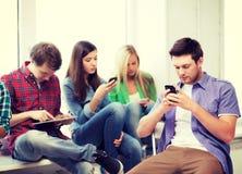 Estudiantes que miran en los dispositivos la escuela Foto de archivo