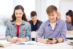 Estudiantes que miran en smartphone la escuela Fotos de archivo