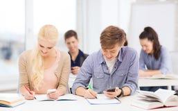 Estudiantes que miran en smartphone la escuela Foto de archivo
