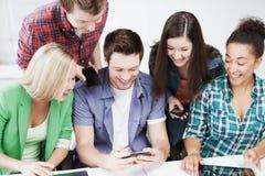 Estudiantes que miran en smartphone la escuela Imágenes de archivo libres de regalías