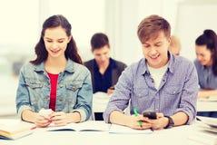 Estudiantes que miran en smartphone la escuela Imagen de archivo libre de regalías
