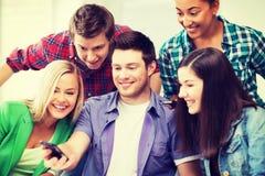 Estudiantes que miran en smartphone la escuela Fotografía de archivo