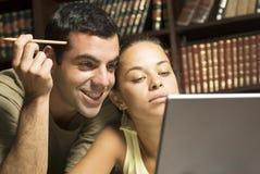 Estudiantes que miran la computadora portátil - horizontal imagen de archivo libre de regalías