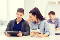 Estudiantes que miran la PC de la tableta en conferencia la escuela Fotos de archivo