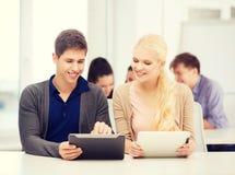 Estudiantes que miran la PC de la tableta en conferencia la escuela Foto de archivo