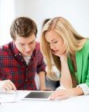 Estudiantes que miran la PC de la tableta la escuela Imagenes de archivo