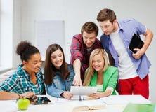 Estudiantes que miran la PC de la tableta la escuela Imágenes de archivo libres de regalías