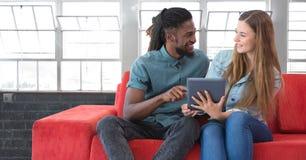 Estudiantes que miran la tableta delante del fondo de las ventanas imagenes de archivo