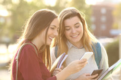 Estudiantes que miran medios en un teléfono elegante Imagenes de archivo