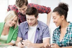 Estudiantes que miran smartphone Foto de archivo libre de regalías