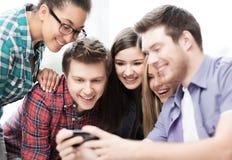 Estudiantes que miran smartphone Imagen de archivo