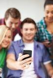 Estudiantes que miran smartphone la escuela Imágenes de archivo libres de regalías