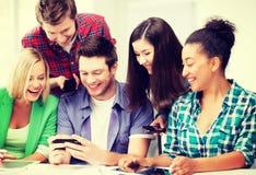 Estudiantes que miran smartphone la escuela Imagenes de archivo