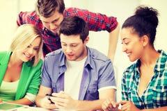 Estudiantes que miran smartphone la escuela Imagen de archivo libre de regalías