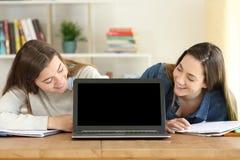 Estudiantes que miran una pantalla de la maqueta del ordenador portátil Fotos de archivo