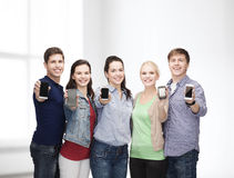 Estudiantes que muestran las pantallas en blanco de los smartphones Fotos de archivo libres de regalías