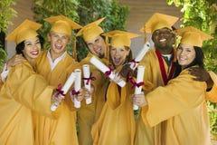 Estudiantes que muestran los diplomas el día de graduación en universidad Foto de archivo