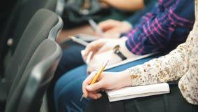 Estudiantes que participan en una conferencia y que toman las notas - gente que escribe en sus cuadernos metrajes