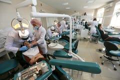 Estudiantes que practican la odontología en maniquíes médicos en una instalación o una universidad de enseñanza imagen de archivo libre de regalías