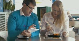 Estudiantes que preparan proyecto de la clase durante el almuerzo almacen de metraje de vídeo