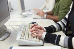 Estudiantes que pulsan en el teclado en clase del ordenador Imagen de archivo libre de regalías