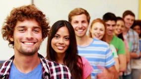 Estudiantes que se colocan en la sala de clase que da los pulgares a la cámara en una línea almacen de metraje de vídeo