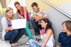 Estudiantes que se divierten con las escaleras de la escuela de la computadora portátil Fotografía de archivo libre de regalías