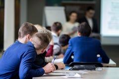 Estudiantes que se inspiran, jovenes 18-20 años, para discutir vivo la conferencia de profesores en la tabla, para tomar un exame foto de archivo libre de regalías