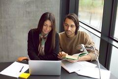 Estudiantes que se preparan para los exámenes junto en biblioteca Foto de archivo libre de regalías
