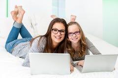 Estudiantes que se relajan con los ordenadores portátiles en cama Imagen de archivo libre de regalías